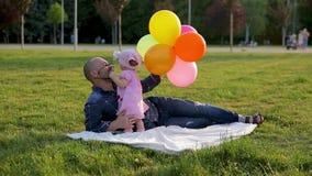 Ojciec w szkłach z balonami i dziecięcej córki kłamstwo na koc w parku córka, wtedy całujemy on i zbiory wideo