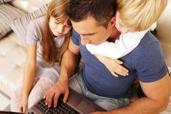 Ojciec z dziećmi pracuje na laptopie Obrazy Royalty Free