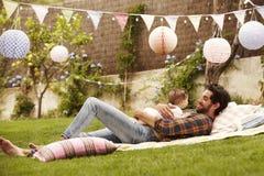 Ojciec Z dzieckiem Relaksuje Na dywaniku W ogródzie Wpólnie Zdjęcie Stock