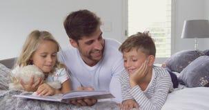 Ojciec z jego dziećmi czyta opowieść rezerwuje w sypialni 4k w domu zdjęcie wideo