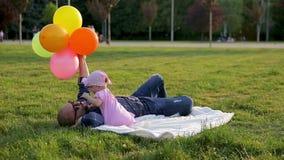Ojciec z kolorowymi balonami kłama na białej koc i jego śliczna dziecięca córka zdejmuje szkła tata i bije on w parku zdjęcie wideo