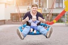 Ojciec z syna obsiadaniem na dużych nowożytnych łańcuchu śmiać się i huśtawce Wychowywa z chłopiec cieszy się huśtać się na seesa obrazy stock
