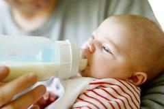 Ojcuje żywieniowej nowonarodzonej dziecko córki z mlekiem w karmiącej butelce Obraz Stock