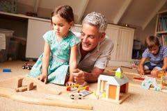 Ojcuje bawić się z dzieciakami i zabawkami w strychowym playroom fotografia stock