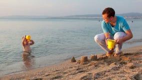 Ojcuje bawić się z jego synem przy plażą zbiory
