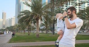 Ojcuje bawić się z synami w lecie w nowożytnym mieście trzyma on i ściska stać w białej koszulce i skrótach zdjęcie wideo