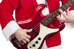 Ojcuje boże narodzenia bawić się czerwoną elektryczną basową gitarę Fotografia Stock