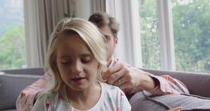 Ojcuje czesać jego córki włosiane na kanapie 4k w domu zdjęcie wideo
