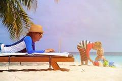 Ojcuje działanie na laptopie podczas gdy dzieciaki bawić się przy plażą obraz royalty free