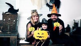 Ojcuje i świętuje, matka i ich syn w kostiumach czarownic, guślarki i kośca chwyta melon w ich rękach, zdjęcie wideo