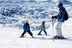 Ojcuje i dwa chłopiec, narciarstwo na słonecznym dniu na halnym szczycie zdjęcie stock