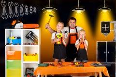 Ojcuje i dwa syna pracuje w ciesielka warsztacie obraz stock