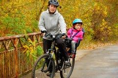 Ojcuje i dzieciak na rowerze, jeździć na rowerze w jesień parku Obrazy Stock