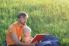 Ojcuje i jego śliczny syn czytająca berbeć książka wpólnie plenerowa Autentyczny stylu życia wizerunek kosmos kopii Zdjęcie Royalty Free