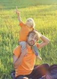 Ojcuje i jego berbecia syn bawić się z zabawkarskim samolotem na lecie f Zdjęcia Stock