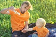 Ojcuje i jego berbecia syn bawić się z zabawkarskim samolotem Rodzinny pinkin na naturze Dzieciństwo lub rodzinny podróży pojęcie Zdjęcia Royalty Free