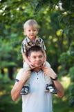 Ojcuje i jego dziecko syn ma zabawę w parku plenerowym Obraz Royalty Free