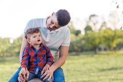 Ojcuje i jego syn ma zabawę outside w lata śmiać się i przytuleniu Ojciec bierze opiekę jego dziecko zdjęcie stock