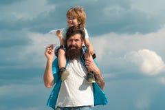 Ojcuje i jego syna dziecka chłopiec bawić się outdoors Szczęśliwy ojciec daje syna plecy przejażdżce na niebie w lecie _ Szcz??li zdjęcie stock