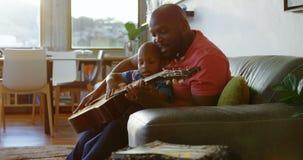 Ojcuje jego syna uczący dlaczego bawić się gitarę w domu 4k zdjęcie wideo