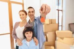 Ojcuje, matka i syn w nowym mieszkaniu z kartonami Ojciec trzyma klucze obraz royalty free