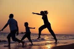 Ojcuje matki i syna bawić się na plaży przy zmierzchu czasem Zdjęcia Stock