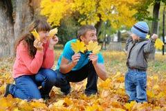 Ojcuje, matki i syna szczęśliwa rodzina w jesieni, kolorów żółtych liście Zdjęcie Royalty Free