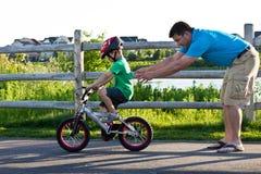 Ojcuje nauczanie syna dlaczego jechać bicykl Obrazy Stock