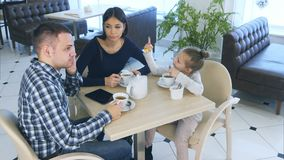Ojcuje opowiadać dzwonić podczas gdy siedzący z jego córką w i żoną kawiarni lub restauraci Macierzysty patrzeć gniewny przy on fotografia stock