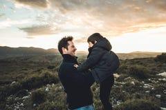 Ojcuje rzucać jego syna w powietrze Pojęcie szczęście i radość między rodzicem i dzieckiem obraz royalty free