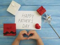 Ojcuje ` s dzień, świętuje czerwonego serce na błękitnym drewnianym tle, dziecka ` s ręki, Obrazy Stock