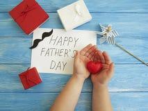 Ojcuje ` s dzień, dziecka ` s ręk projekta gratulacyjny czerwony serce na błękitnym drewnianym tle Zdjęcie Stock