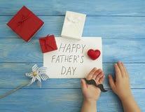 Ojcuje ` s dzień, dziecka ` s ręki, czerwony serce na błękitnym drewnianym tle Zdjęcie Stock