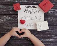 Ojcuje ` s dzień, dziecka ` s ręki, czerwony serce na czarnym drewnianym tle Zdjęcie Stock