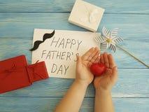 Ojcuje ` s dzień, dziecka ` s ręki, projekta gratulacyjny czerwony serce na błękitnym drewnianym tle Obraz Royalty Free