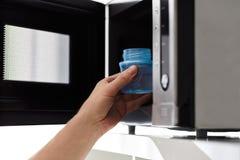Ojcuje stawiać dziecko butelkę w mikrofalę Zdjęcia Stock