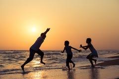 Ojcuje syna i córki bawić się na plaży przy zmierzchu czasem Zdjęcie Royalty Free
