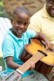 Ojcuje teaaching jego jego syna bawić się gitarę Fotografia Royalty Free