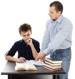 Ojcuje trwanie pobliskiego syna biurko pomaga on robi jego pracie domowej zdjęcie royalty free