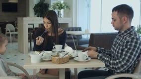 Ojcuje używać jego laptop w kawiarni podczas gdy siedzący z jego córką i żoną Kobiety zrozumienie i no zakłócać on obrazy stock