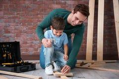 Ojcuje uczyć jego małego syna prowadnikowy gwóźdź zdjęcia royalty free