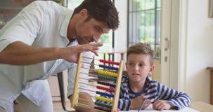 Ojcuje uczyć jego syn matematykę przy stołem w wygodnym domu 4k zdjęcie wideo