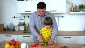 Ojcuje uczyć jego syna w domu kotlecików warzywa w kuchni Rżnięty ogórek Zwolnione tempo Szczęśliwy rodzinny narządzanie zbiory wideo