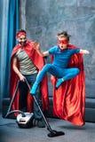 Ojcuje w bohatera kostiumowym vacuuming dywanie podczas gdy syn w bohatera kostiumu doskakiwaniu obraz stock