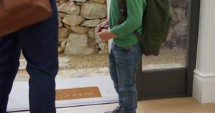 Ojcuje wiązać jego synów shoelaces przy drzwi w wygodnym domu 4k zbiory wideo