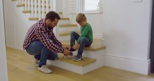 Ojcuje wiązać jego synów shoelaces w wygodnym domu 4k zbiory wideo