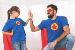 Ojcuje z córką w czerwonych i błękitnych kostiumach bohaterzy One w maskach i deszczowach obrazy royalty free