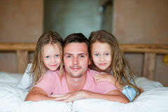 Ojcuje z dwa uroczymi małymi dziewczynkami ma zabawę w łóżkowy ono uśmiecha się zdjęcia stock