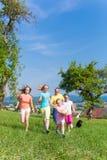 Ojcuje z dziećmi biega na zielonej łąkowej trawie Obrazy Royalty Free