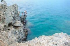 Ojcuje z dziećmi na skale blisko morza zarygluj składu pojęcia rodziny orzechy Hol zdjęcia royalty free